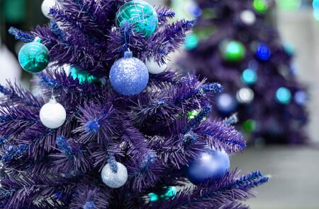 Decorated blue christmas tree with reflection of sparkling second christmas tree. Bright blue Christmas wallpaper with two elegant conifers, one out of focus. Wallpaper, congratulation, 2020, new year. Stock fotó