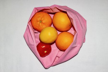 Clean food concept, zero waste, vegetarianism. Fresh fruits in an eco cotton bag on a white cloth background. Copy space, flat lay, top view, isolate. Orange, lemon, mandarin and tomato