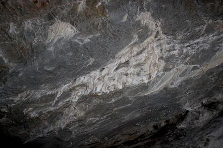 Gray karst cave. Rock formations in the cave, stalactites and stalagmites. Abstract gray grunge background. Stone texture background. Spotted abstract stone. Russia, Bashkortostan, a fairy cave.