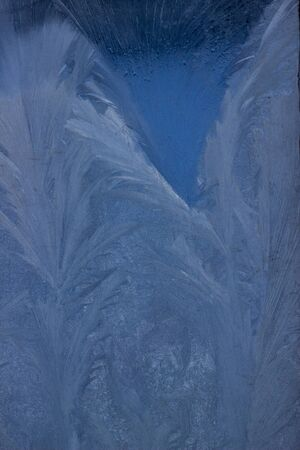 The texture of the frosty patterns. Winter frosty blue patterns on the window pane. Ice background for christmas and new year. Macro Soft Focus