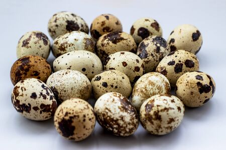 Group of quail eggs on a white background. A lot of spotted eggs on a light background, close-up Фото со стока
