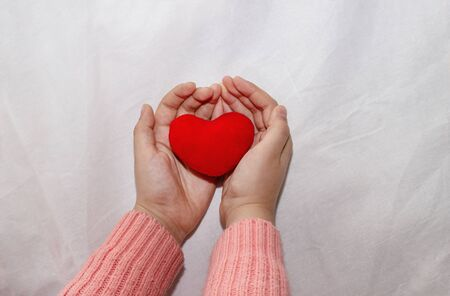 Hands of a child with a red heart on a light cloth. Girl hands hold a red heart isolated on a white background. Concept for mother's day, maintaining health, care. Valentine's Day 免版税图像 - 139602498