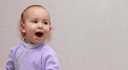 Banner, Copy Space. Toddler with open mouth. A little girl in a purple jumper screams joyfully. Beautiful enthusiastic child with brown eyes on a light background. Portrait of an emotional boy.