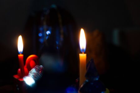 The dance of divination, magic, clairvoyance, a ritual in the night. Soft focus for mystery. Burning candles in the dark with paraphernalia of magic, copy space. Artistically blurry.