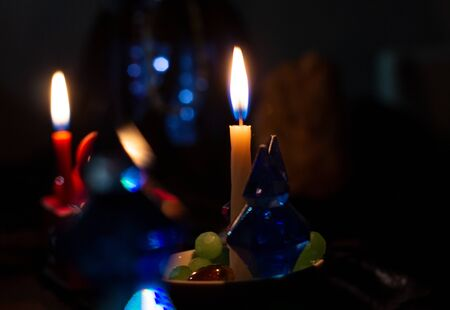 Fortune-telling attributes and two candles burn in a dark room. The ritual of mysticism. clairvoyance. Artistically blurry, out of focus, mystery, copy space