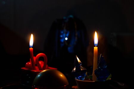 Attributes of witchcraft and two candles burn in a dark room. The ritual of mysticism. clairvoyance. Artistically blurry, out of focus, mystery, copy space