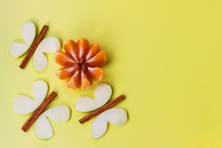 Creative fruit dessert funny apple butterfly shape and mandarin flower. Copy space, flat lay. Beautiful fruit fantasy, apple and cinnamon butterfly, mandarin and peanut flower.