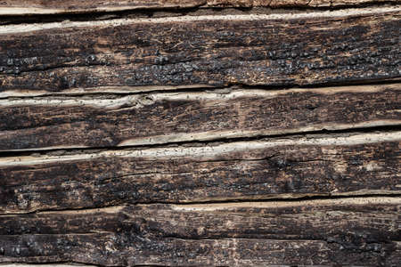 Background - the texture of burnt logs of the wall of a wooden house. Burnt wood charred texture of a log house. close-up. The walls of a wooden house after a fire. Charred coals. Summer. Sunny day.