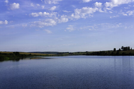 Lake at sky with a blue reflection and green hills on the background photo