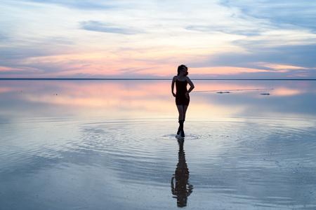 Słone jezioro. Dziewczyna stojąca w wodzie o zachodzie słońca. Odbicie w wodzie. Zdjęcie Seryjne