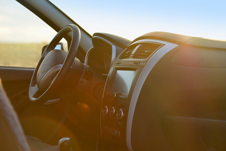 The steering wheel and the panel of a salon car in sunlight