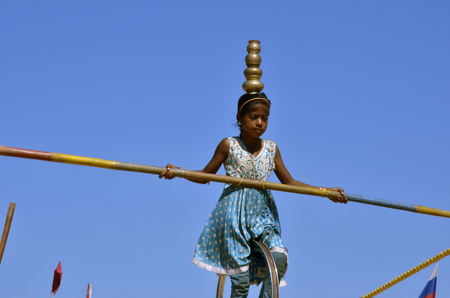 Panaji, Goa, India - 31/12/2011: A girl from India on a rope on a background of blue sky with a pole and a vase on her head in a blue dress Editorial