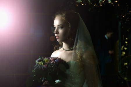 Wedding portrait. Portrait of a girl in a wedding dress with a veil on a dark background. Bride with bouquet of flowers