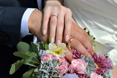 The hands of the newlyweds with rings against the background of a bouquet of flowers. Hands of newlyweds