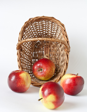 palatable: Wicker basket with apples on white background Stock Photo