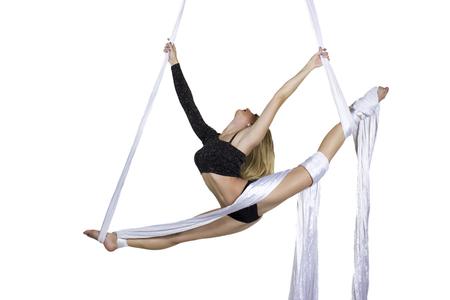 Pretty woman - aerialist doing acrobatic tricks on aerial silks Stock Photo