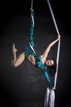 strong women: Aerialist woman doing some flexibility and strength tricks on silks Stock Photo