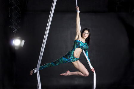 flexibility: Aerialist woman doing some flexibility and strength tricks on silks Stock Photo