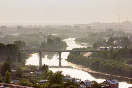 rule of thirds: Beautiful cityscape of small town with river and railway in summer, golden hour, Uchta