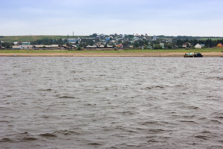 Beautiful summer landscape with river and old russian village Ust-Tsilma