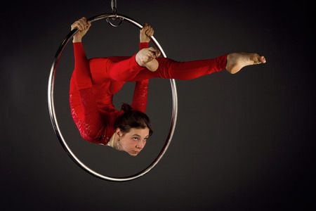 Attractive aerialist woman exercising on aerial ring (lyra)