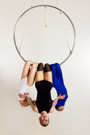 Young woman`s trio doing som acrobatic tricks on aerial luster Stock Photo