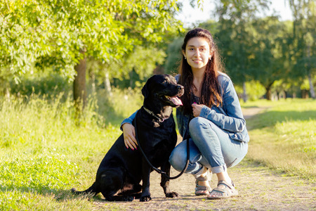Beautiful young woman posing with her black labrador retriever on the pathway at summer