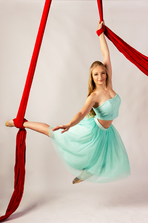 Beautiful aerialist girl doing acrobatic and flexible tricks on red aerial silks (tissues) on white background Stock Photo