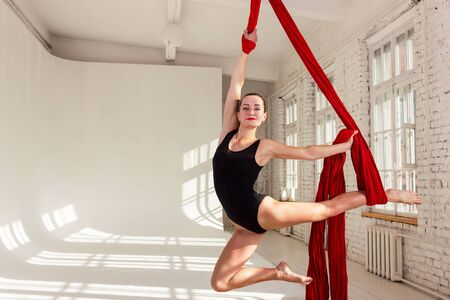 Beautiful aerialist girl doing acrobatic and flexible tricks on red aerial silks (tissues) on white brick and white wall on background