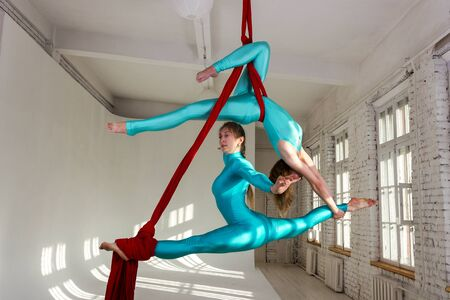 Beautiful aerialists girls doing acrobatic and flexible tricks on red aerial silks (tissues) on white brick and white wall on background