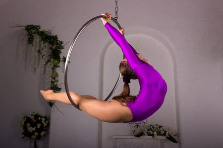 Beautiful aerialist girl doing acrobatic and flexible tricks on aerial ring (lyra) in photostudio with falseness arch and decorations on white wall