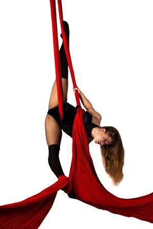 Beautiful aerialist girl doing acrobatic and flexible tricks on red aerial silks (tissues) isolated on white background