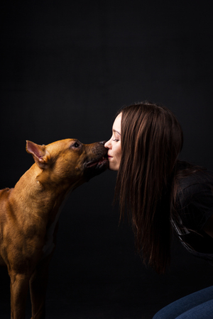 Girl kisses with red american staffordshire terrier indoor on black background