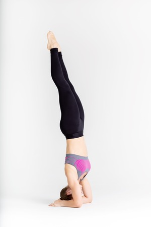 Full length portrait of a young sportwoman stretching muscles while sitting on the floor isolated over white background