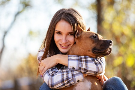 Beautiful woman with her american staffordshire terrier walks outdoor in autumn park 写真素材 - 114580527