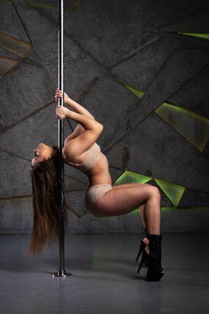 Beautiful girl doing acrobatic and flexible tricks on pole at dance studio