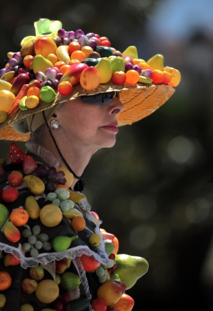 Elderly woman in costume decorated with artificial fruits  photo