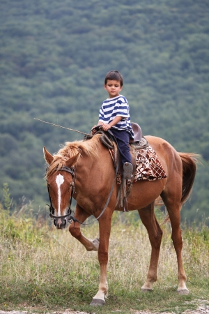 Boy riding horse in Crimea mountains  photo
