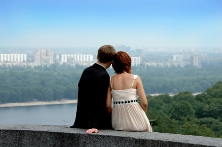 Couple of young man and woman  sitting on height and looking at cityscape. photo