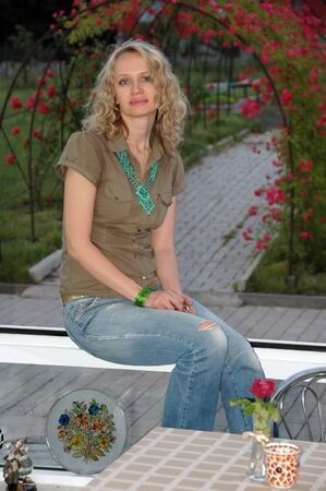 Beautiful woman sitting on sill of big window against garden view. Stock Photo