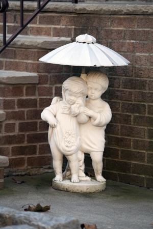 Little sculpture of children under umbrella  photo