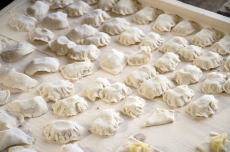 Raw dumplings with potato on carving board  Stock Photo - 23032556