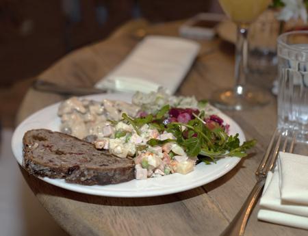 huzarensalade: Plaat met Russische salade, sneetje zoete bruin brood en vinaigrette belegd met rucola