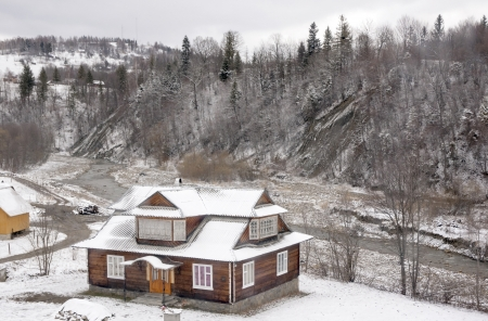 front stoop: Detached house near river in Carpathian mountains  in wintertime   Editorial