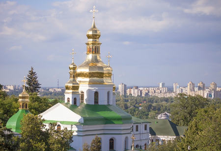 Gilded cupolas of Caves Monastery in Kiev against modern buildings of the city  photo