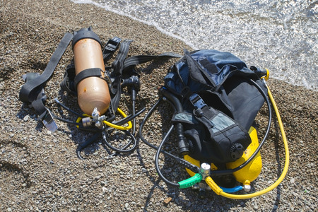 Set of Scuba Diving equipment on the pebble beach near water