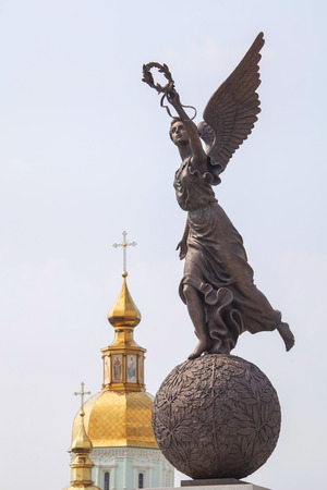 named person: Monument to goddess Nike on sphere against cupolas of the church in Kharkov,Ukraine