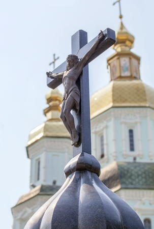 tortured body: Sculpture of Crucified Christ against cupolas of church