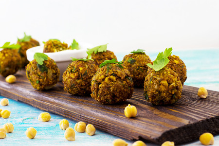 Falafel on a wooden board. The background is light. Archivio Fotografico