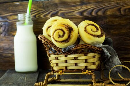 Snails with cinnamon. Wooden background. Stock Photo